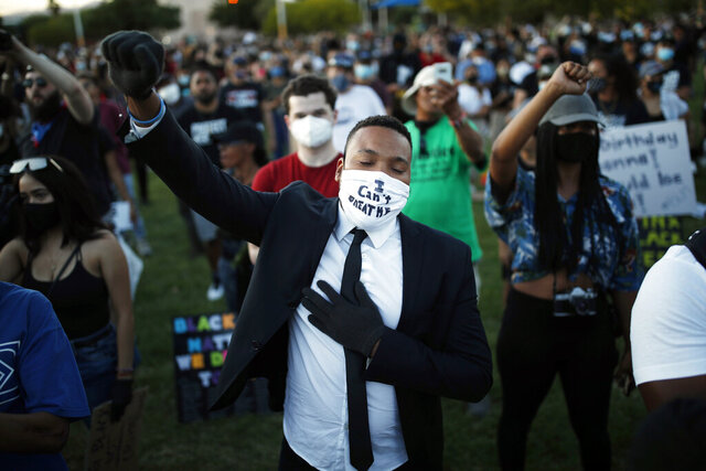 People raise their fists during a rally, Friday, June 5, 2020, in Las Vegas, against police brutality sparked by the death of George Floyd, a black man who died after being restrained by Minneapolis police officers on May 25. (AP Photo/John Locher)