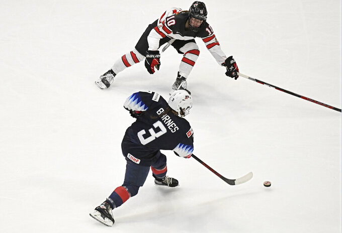 United States' Cayla Barnes scores a goal as Canada's Sarah Fillier, top defends in the first period of a women's hockey game in a pre-Olympic Games series Monday, Oct. 25, 2021, in Hartford, Conn. (AP Photo/Jessica Hill)