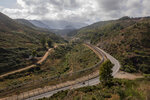 A motorcycle rides on the Spanish side of the border fence that separates Spain and Morocco in the Spanish enclave of Ceuta, Thursday, June 3, 2021. (AP Photo/Bernat Armangue)