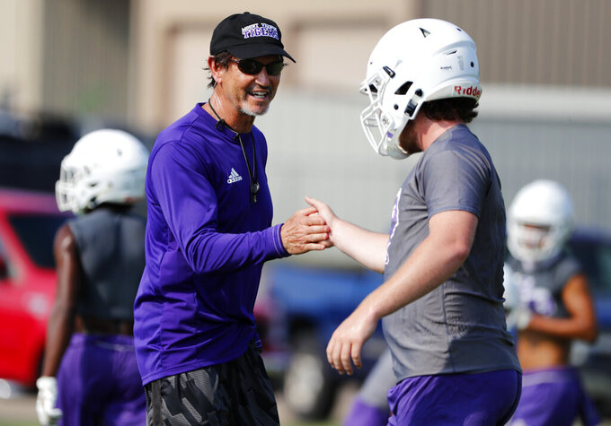 Art Briles, left, motivates a player during a practice at Mount Vernon High School, Monday, Aug. 5, 2019, in Mount Vernon, Texas. (AP Photo/Tony Gutierrez)