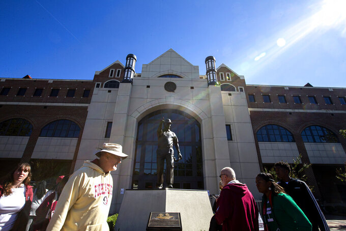 Florida State fans walk past the statue of former coach Bobby Bowden before an NCAA college football game against Miami in Tallahassee, Fla., Saturday, Nov. 2, 2019. (AP Photo/Mark Wallheiser)