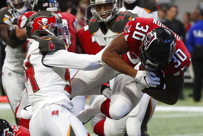 Atlanta Falcons running back Qadree Ollison (30) leaps into the end zone against Tampa Bay Buccaneers outside linebacker Lavonte David (54) during the first half of an NFL football game, Sunday, Nov. 24, 2019, in Atlanta. (AP Photo/John Bazemore)
