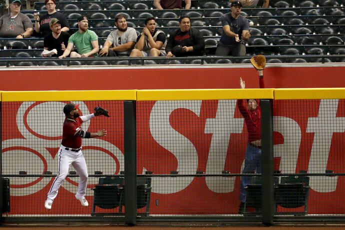 A fan tries to get a glove on a solo home run hit by Miami Marlins' Austin Dean during the fourth inning of a baseball game as Arizona Diamondbacks' Abraham Almonte looks on Wednesday, Sept. 18, 2019, in Phoenix. (AP Photo/Matt York)