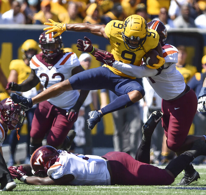 West Virginia wide receiver Isaiah Esdale (9) leaps over a Virginia Tech player during the first half of an NCAA college football game in Morgantown, W.Va., Saturday, Sept. 18, 2021. (AP Photo/William Wotring)