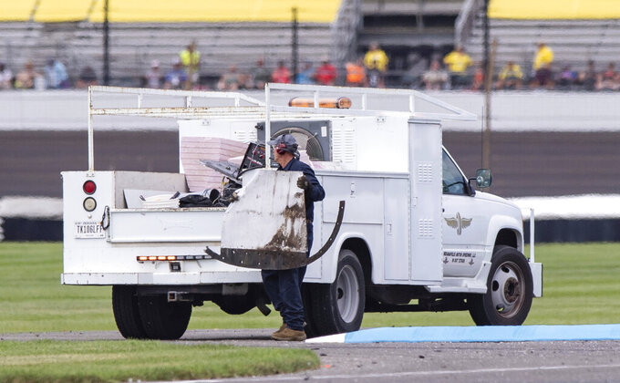 A member of the track crew removes a part of the car of Aric Almirola from the track during a NASCAR Cup Series auto race at Indianapolis Motor Speedway, Sunday, Aug. 15, 2021, in Indianapolis. (AP Photo/Doug McSchooler)