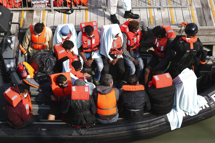 A group of people, thought to be migrants wait on a Border Force rib to come ashore at Dover marina in Kent, England after a small boat incident in the English Channel, Tuesday Sept. 22, 2020. (Gareth Fuller/PA via AP)