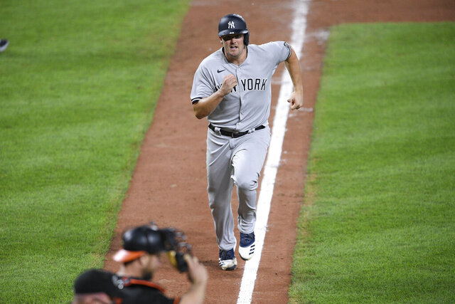 New York Yankees' Jonathan Holder runs home to score on a single by Miguel Andujar during the ninth inning of the first baseball game of a doubleheader against the Baltimore Orioles, Friday, Sept. 4, 2020, in Baltimore. The Yankees won 6-5 in nine innings. (AP Photo/Nick Wass)