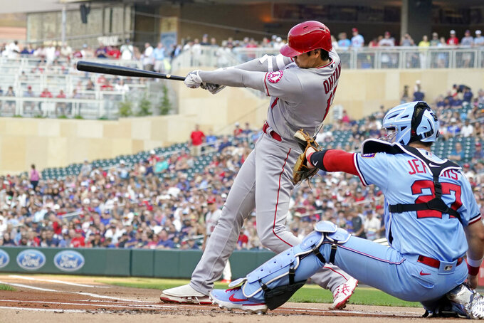 Los Angeles Angels' Shohei Ohtani, left, follows through on a double off Minnesota Twins pitcher Jose Berrios in the first inning of a baseball game, Saturday, July 24, 2021, in Minneapolis. (AP Photo/Jim Mone)