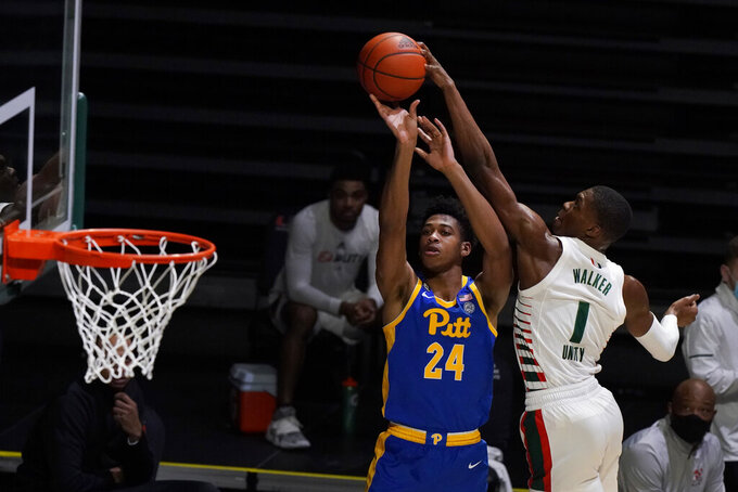 Pittsburgh guard William Jeffress (24) takes a shot against Miami forward Anthony Walker (1) during the first half of an NCAA college basketball game, Wednesday, Dec. 16, 2020, in Coral Gables, Fla. (AP Photo/Wilfredo Lee)