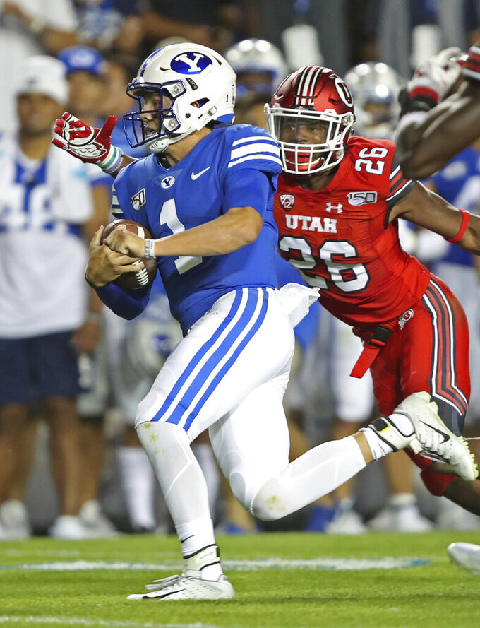 BYU quarterback Zach Wilson (1) runs past Utah defensive back Terrell Burgess (26) for a first down during the first half of an NCAA college football game Thursday, Aug. 29, 2019, in Provo, Utah. (AP Photo/George Frey)