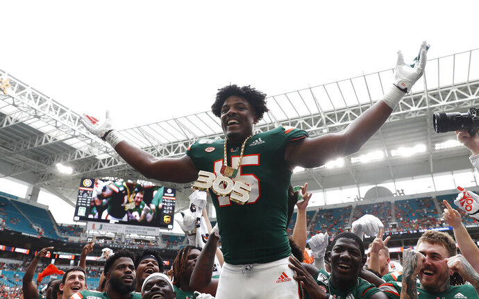 Miami defensive lineman Gregory Rousseau (15) celebrates a turnover and wears the turnover chain during the first half of an NCAA college football game against Central Michigan, Saturday, Sept. 21, 2019, in Miami Gardens, Fla. (AP Photo/Brynn Anderson)