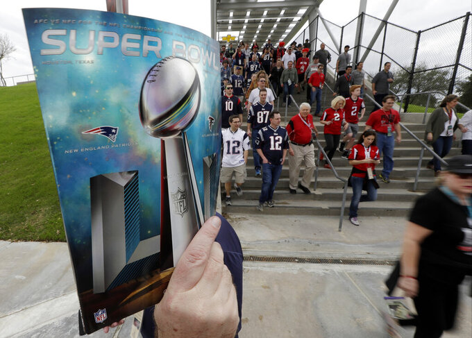 FILE - In this Feb. 5, 2017, file photo, a sales person holds up a program as fans arrive at NRG Stadium before NFL football's Super Bowl 51 between the Atlanta Falcons and the New England Patriots in Houston. of you're headed to the Super Bowl some year in the future, and you're wondering how much cash you'll need for the big game. No worries: During its sponsorship renewal with the NFL through the 2025 season, Visa envisions the first cashless Super Bowl. (AP Photo/David J. Phillip, File)