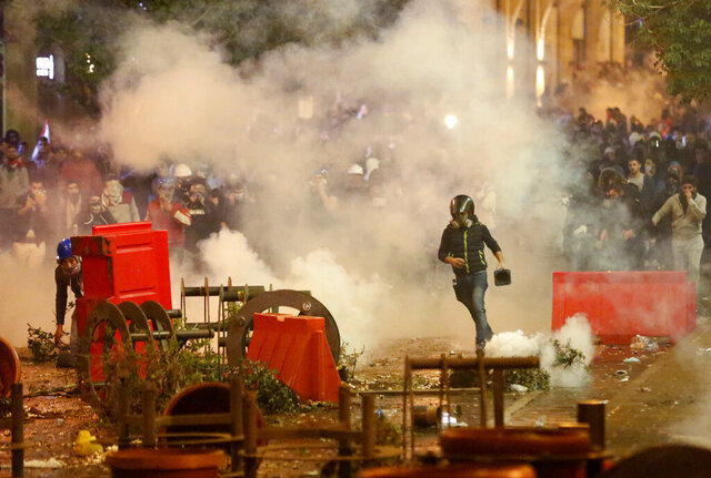 Anti-government protesters clash with the riot police, during a protest near the parliament square, in downtown Beirut, Lebanon, Sunday, Dec. 15, 2019. Lebanese security forces fired tear gas, rubber bullets and water cannons Sunday to disperse hundreds of protesters for a second straight day, ending what started as a peaceful rally in defiance of the toughest crackdown on anti-government demonstrations in two months. (AP Photo/Hussein Malla)