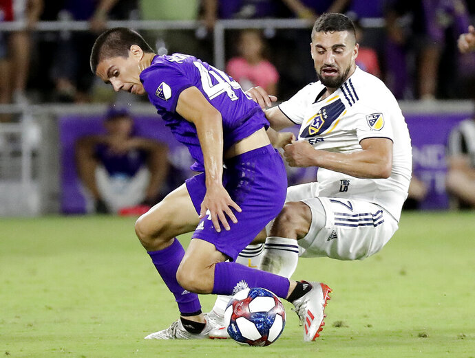 Orlando City's Joao Moutinho, left, and LA Galaxy's Sebastian Lletget compete for possession of the ball during the second half of an MLS soccer match Friday, May 24, 2019, in Orlando, Fla. (AP Photo/John Raoux)