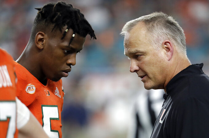 Miami quarterback N'Kosi Perry, left, talks Miami head coach Mark Richt during the second half of an NCAA college football game against Pittsburgh, Saturday, Nov. 24, 2018, in Miami Gardens, Fla. Miami won 24-3. (AP Photo/Lynne Sladky)