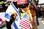 Hamas supporters burn painted posters of Americans and Israeli flags during a protest against the Mideast plan announced by U.S. President Donald Trump, after the Friday prayer at the main road in Gaza City, Friday, Feb. 14, 2020. (AP Photo/Adel Hana)
