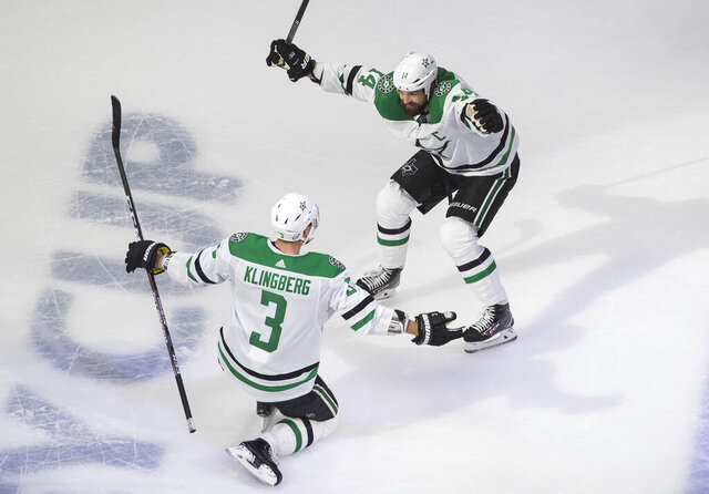 Dallas Stars' John Klingberg (3) and Jamie Benn (14) celebrate a goal against the Calgary Flames during overtime in Game 4 of an NHL hockey first-round playoff series, Sunday, Aug. 16, 2020, in Edmonton, Alberta. (Jason Franson/The Canadian Press via AP)