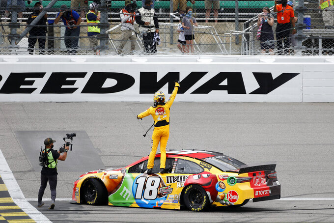 Kyle Busch, center, reacts after winning a NASCAR Cup Series auto race at Kansas Speedway in Kansas City, Kan., Sunday, May 2, 2021. (AP Photo/Colin E. Braley)