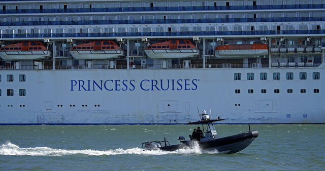 FILE - In this Friday, March 13, 2020, file photo, an Oakland Police boat patrols the waters beside the Grand Princess cruise ship, which remains docked at the Port of Oakland in Oakland, Calif. Nearly 650 crew members of the Grand Princess have completed their 14-day quarantine, ending a month-long period of self-isolation that began when the cruise ship was struck with the coronavirus. The cruise line said the crew members can finally leave their staterooms Saturday, April 4, and roam around the ship as long as they wear personal protective equipment and stay at least six feet from each other. The ship will leave San Francisco Bay and sail out to sea for several days of routine marine operations. (AP Photo/Ben Margot, File)