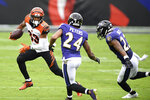 Cincinnati Bengals wide receiver Tyler Boyd (83) runs with the ball as Baltimore Ravens cornerback Marcus Peters (24) and cornerback Jimmy Smith (22) defend during the first half of an NFL football game, Sunday, Oct. 11, 2020, in Baltimore. (AP Photo/Nick Wass)