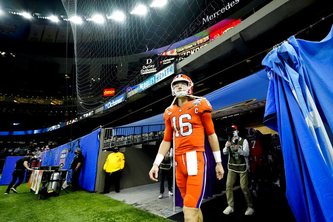 Clemson quarterback Trevor Lawrence walks onto the field before the Sugar Bowl NCAA college football game against Ohio State Friday, Jan. 1, 2021, in New Orleans. (AP Photo/Gerald Herbert)