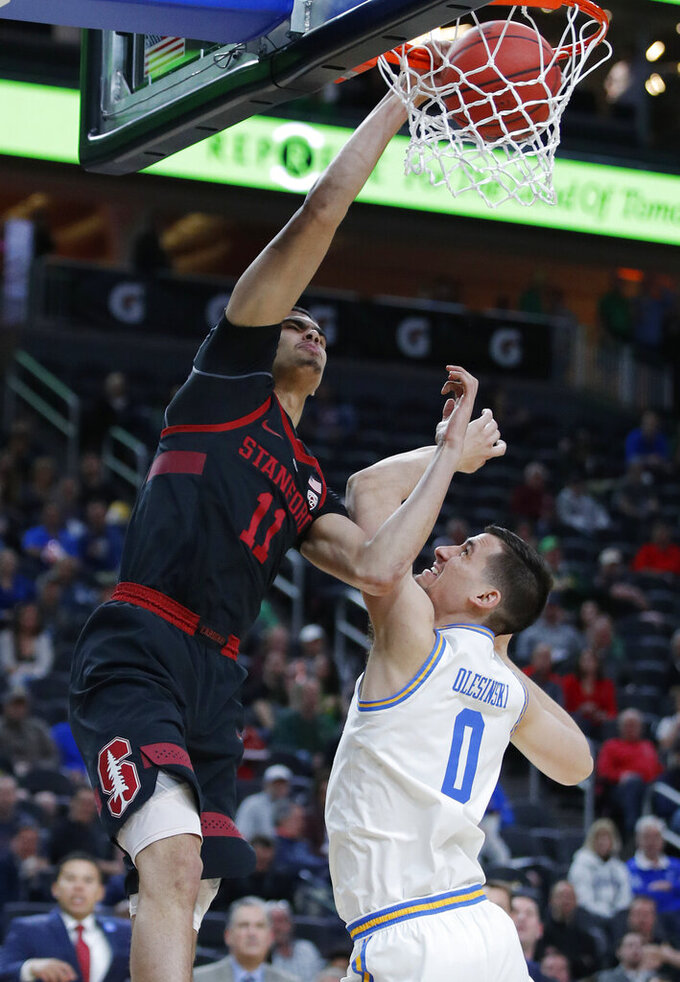 Stanford's Jaiden Delaire dunks over UCLA's Alex Olesinski during the second half of an NCAA college basketball game in the first round of the Pac-12 men's tournament, Wednesday, March 13, 2019, in Las Vegas. (AP Photo/John Locher)