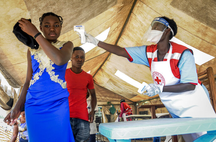FILE - In this Friday, June 14, 2019 file photo, people coming from Congo have their temperature measured to screen for symptoms of Ebola, at the Mpondwe border crossing with Congo, in western Uganda. Ugandan health authorities on Thursday, Aug. 29, 2019 said a 9-year-old Congolese child has tested positive for Ebola in Uganda, after being identified and screened at the official Mpondwe border crossing, and was then taken to an isolation unit in the Ugandan border town of Bwera in Kasese district. (AP Photo/Ronald Kabuubi, File)