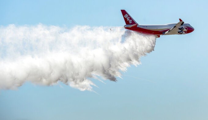 FILE - In this May 5, 2016, file photo, a Boeing 747-400 Global SuperTanker drops half a load of its 19,400-gallon capacity during a ceremony at Colorado Springs, Colo. The world's largest firefighting plane has been shut down just as Western states prepare for a wildfire season that fire officials fear could be worse than the average year. Tara Lee, a spokeswoman for Washington Gov. Jay Inslee, said via email Friday, April 23, 2021, that the state's Department of Natural Resources was alerted to the shutdown of the worlds' largest firefighting plane called the Global SuperTanker.(Christian Murdock/The Gazette via AP, File)