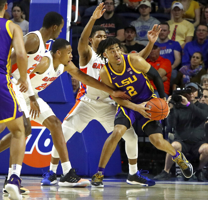 LSU forward Trendon Watford (2) tries to keep the ball away from Florida defenders during an NCAA college basketball game, Wednesday, Feb. 26, 2020 in Gainesville, Fla.  (Brad McClenny/The Gainesville Sun via AP)