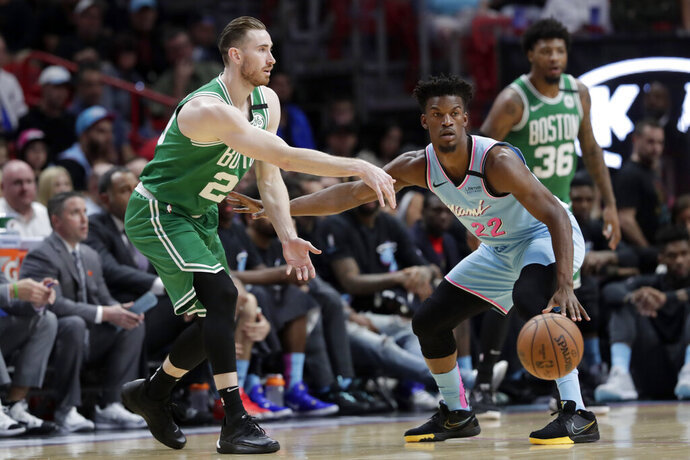 Boston Celtics forward Gordon Hayward, left, passes as Miami Heat forward Jimmy Butler (22) defends during the first half of an NBA basketball game, Tuesday, Jan. 28, 2020, in Miami. (AP Photo/Lynne Sladky)