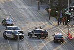 In this Wednesday, May 15, 2019 photo, authorities investigate the scene of a shooting at the Valley Transit Center in Appleton, Wis. A firefighter responding to a medical emergency was killed in the shooting at a Wisconsin bus station that left several others injured, officials said. (Dan Powers/The Post-Crescent via AP)