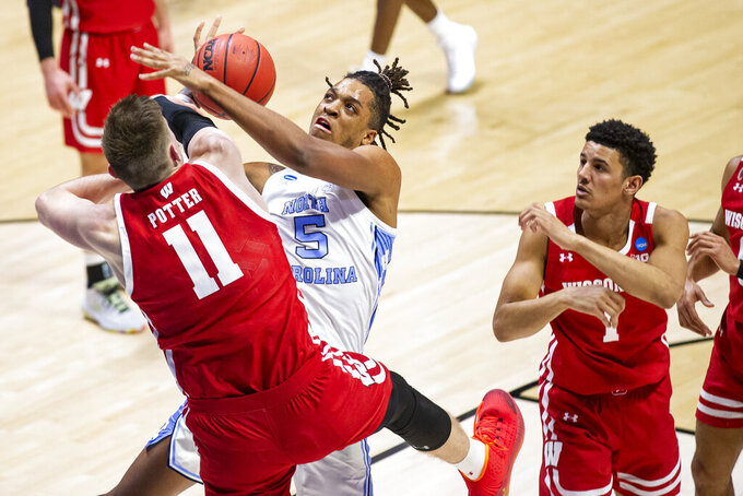 North Carolina's Armando Bacot (5) has a shot knocked away by Wisconsin's Micah Potter (11) during the second half of a first-round game in the NCAA men's college basketball tournament, Friday, March 19, 2021, at Mackey Arena in West Lafayette, Ind. (AP Photo/Robert Franklin)
