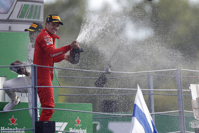 Ferrari driver Charles Leclerc of Monaco sprays champagne as celebrates on podium after winning the Formula One Italy Grand Prix at the Monza racetrack, in Monza, Italy, Sunday, Sept. 8, 2019. (AP Photo/Luca Bruno)