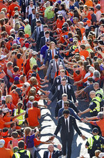 """FILE - In this Sept. 21, 2019, file photo, Clemson quarterback Trevor Lawrence, center, and teammates greet the fans during """"Tiger Walk"""" before the team's NCAA college football game against Charlotte in Clemson, S.C. Clemson athletic director Dan Radakovich, whose school competes in the Atlantic Coast Conference and has had one of the most successful football programs in the country in recent years, said that while he doesn't believe name, image and likeness compensation will damage competitive balance, he is sympathetic to schools with smaller budgets who have those concerns. (AP Photo/Richard Shiro, File)"""
