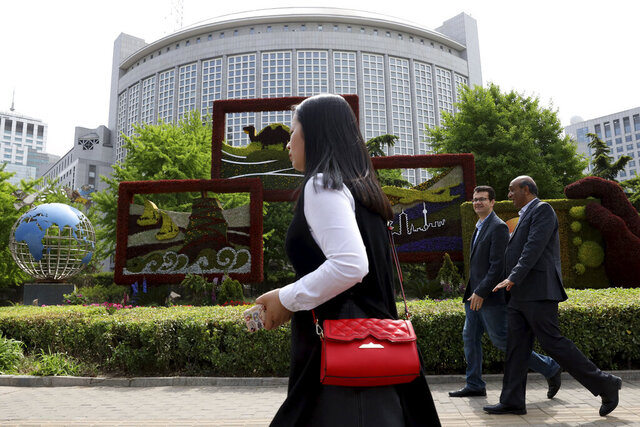 In this April 19, 2019, photo, foreigners pass by the Chinese Foreign Ministry in Beijing, China. China on Wednesday, Feb. 19, 2020 said it has revoked the press credentials of three reporters for the U.S. newspaper Wall Street Journal over a headline for an opinion column deemed by the government to be racist and slanderous. (AP Photo/Ng Han Guan)