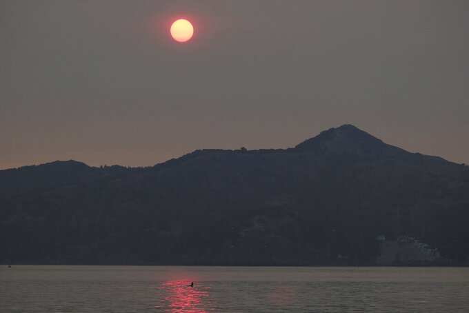 A rower goes past Angel Island and the sun rising behind in smoke from wildfires Wednesday, Aug. 19, 2020, in Sausalito, Calif. Thousands of people were under orders to evacuate in regions surrounding the San Francisco Bay Area Wednesday as nearly 40 wildfires blazed across the state amid a blistering heat wave now in its second week. Smoke blanketed the city of San Francisco. (AP Photo/Eric Risberg)