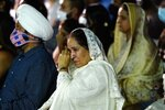 Harjinder Kaur Sodhi, wife of murder victim Balbir Singh Sodhi, wipes a tear away at a memorial service on the 20th anniversary of the murder of Balbir Singh Sodhi, as she sits next to Rana Singh Sodhi, left, brother of Balbir, Wednesday, Sept. 15, 2021, in Mesa, Ariz. Sikh businessman Balbir Singh Sodhi was helping plant a flower bed at his Arizona gas station when he was shot dead by a man seeking to avenge 9/11. Mistaken for an Arab Muslim because of his turban and beard, Sodhi was the first person to die in a wave of bias crimes unleashed by the attacks. (AP Photo/Ross D. Franklin)