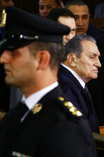 Former Egyptian President Hosni Mubarak, center, arrives with his sons Alaa, left, and Gamal, right, to testify, in a courtroom at the National Police Academy, in Cairo, Egypt, Wednesday, Dec. 26, 2018. Two former Egyptian presidents appeared Wednesday in the same Cairo courtroom, with Mubarak testifying in a retrial of Mohammed Morsi on charges related to prison breaks at the height of the 2011 uprising that toppled Mubarak. (AP Photo/Ahmed Abdel Fattah)
