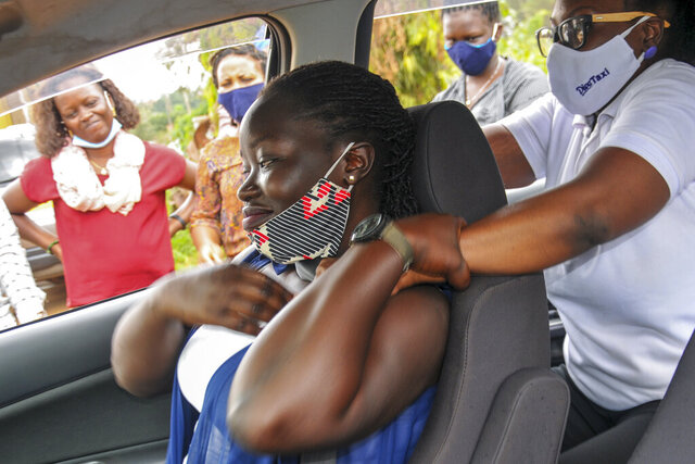Rebecca Makyeli, right, spokeswoman for Uganda's new all-female ride-hailing service Diva Taxi, trains new drivers in self-defense skills in Kampala, Uganda Monday, Sept. 28, 2020. Uganda's latest ride-hailing service Diva Taxi has recruited over 70 drivers ranging from college students to mothers wishing to make good use of their secondhand cars, breaking the mold in the socially conservative country by hiring only female drivers. (AP Photo/Ronald Kabuubi)