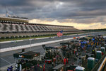 Racers speed down the front straight between the empty grandstand and their crews that are stationed along pit row as the sun goes down during a NASCAR Cup Series auto race at Pocono Raceway, Sunday, June 28, 2020, in Long Pond, Pa. (AP Photo/Matt Slocum)