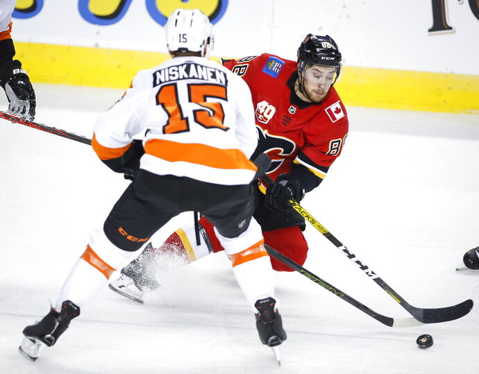 Philadelphia Flyers' Matt Niskanen, left, checks Calgary Flames' Andrew Mangiapane during the first period of an NHL hockey game Tuesday, Oct. 15, 2019, in Calgary, Alberta. (Jeff McIntosh/The Canadian Press via AP)