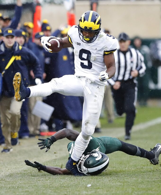 Michigan wide receiver Donovan Peoples-Jones (9) jumps over Michigan State safety Tre Person (24) enroute to a 79-yard touchdown run during the second half of an NCAA college football game, Saturday, Oct. 20, 2018, in East Lansing, Mich. (AP Photo/Carlos Osorio)