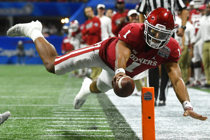 Oklahoma quarterback Jalen Hurts (1) scores a touchdown against LSU during the second half of the Peach Bowl NCAA semifinal college football playoff game, Saturday, Dec. 28, 2019, in Atlanta. (AP Photo/John Amis)