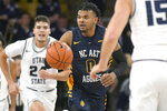 North Carolina A&T guard Andre Jackson (0) brings the ball downcourt as Utah State guard Diogo Brito (24) and guard Abel Porter (15) defend during the first half of an NCAA college basketball game Friday, Nov. 15, 2019, in Logan, Utah. (AP Photo/Eli Lucero)