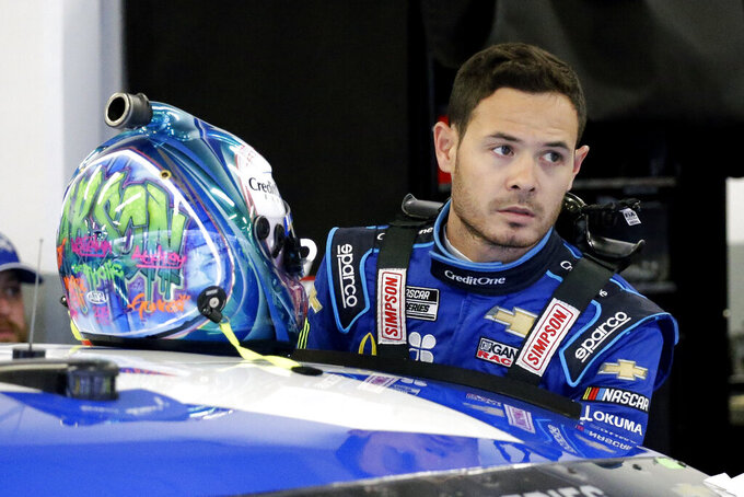 FILE - In this Feb. 14, 2020, file photo, Kyle Larson gets ready to climb into his car to practice for the NASCAR Daytona 500 auto race at Daytona International Speedway in Daytona Beach, Fla. Kyle Larson used a racial slur on a live stream Sunday. April 12, 2020, during a virtual race — the second driver in a week to draw scrutiny while using the online racing platform to fill time during the coronavirus pandemic.(AP Photo/Terry Renna, File)
