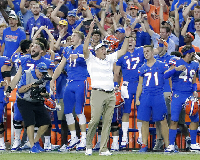 FILE - In this Oct. 6, 2018, file photo, Florida head coach Dan Mullen, center, celebrates with players on the sidelines during the final moments of an NCAA college football game against LSU, in Gainesville, Fla. Mullen opened his first team meeting this week talking about handling success. He'll find out Saturday if anyone was paying attention.(AP Photo/John Raoux, File)