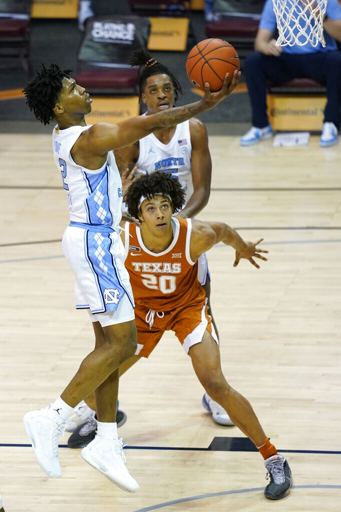 North Carolina guard Caleb Love (2) leaps to the basket over Texas forward Jericho Sims (20) in the second half of an NCAA college basketball game for the championship of the Maui Invitational, Wednesday, Dec. 2, 2020, in Asheville, N.C. Texas won 69-67. (AP Photo/Kathy Kmonicek)