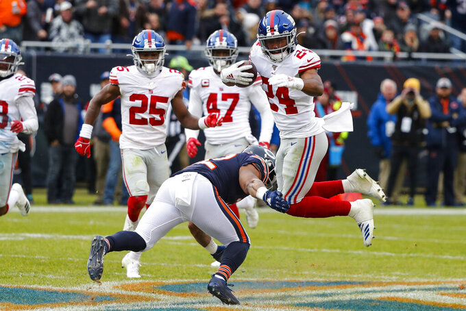 New York Giants cornerback Julian Love (24) is tacked by Chicago Bears running back David Montgomery (32) after an interception during the second half of an NFL football game in Chicago, Sunday, Nov. 24, 2019. (AP Photo/Charles Rex Arbogast)