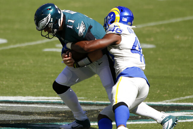 Philadelphia Eagles' Carson Wentz, left, is tackled by Los Angeles Rams' Obo Okoronkwo during the first half of an NFL football game, Sunday, Sept. 20, 2020, in Philadelphia. (AP Photo/Laurence Kesterson)
