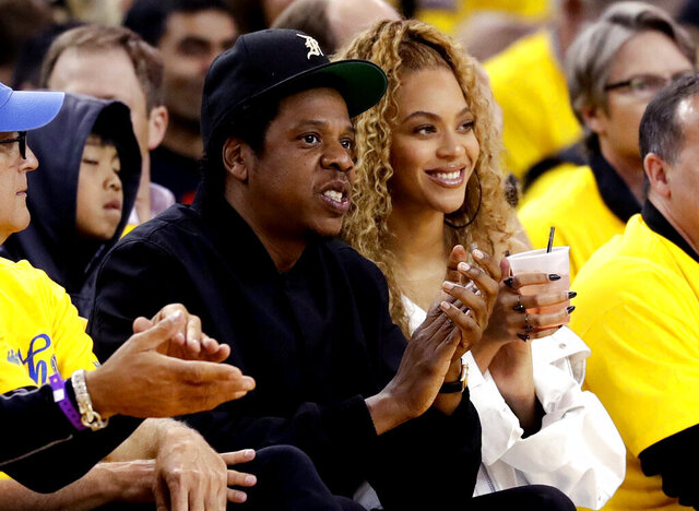 FILE - In this April 28, 2018, file photo, Jay-Z and Beyonce watch Game 1 of an NBA basketball second-round playoff series between the Golden State Warriors and the New Orleans Pelicans in Oakland, Calif. Several top record labels organized Black Out Tuesday on June 2, 2020 as riots erupted around the world sparked by Floyd's death as well as the killings of Ahmaud Arbery and Breonna Taylor. Musicians including Rihanna, Beyoncé, Taylor Swift, Lil Nas X, Demi Lovato, Post Malone and Harry Styles have spoken out following Floyd's death and the worldwide riots. (AP Photo/Marcio Jose Sanchez, File)